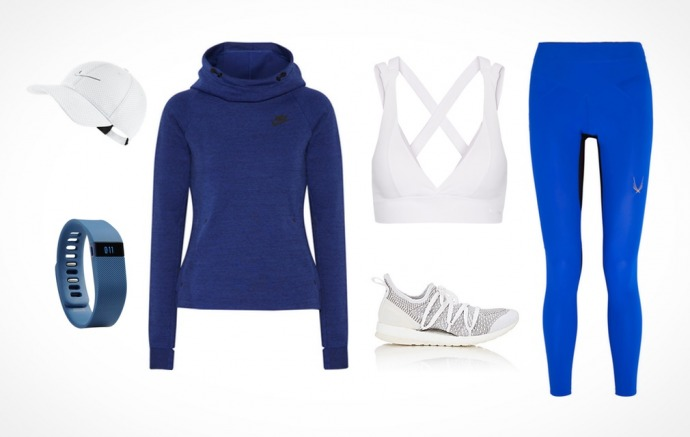 A combination of fitness clothing featuring blue leggings, a white sports bra, a blue Nike sweatshirt, white sneakers, a white baseball hat, and a blue fitness tracker